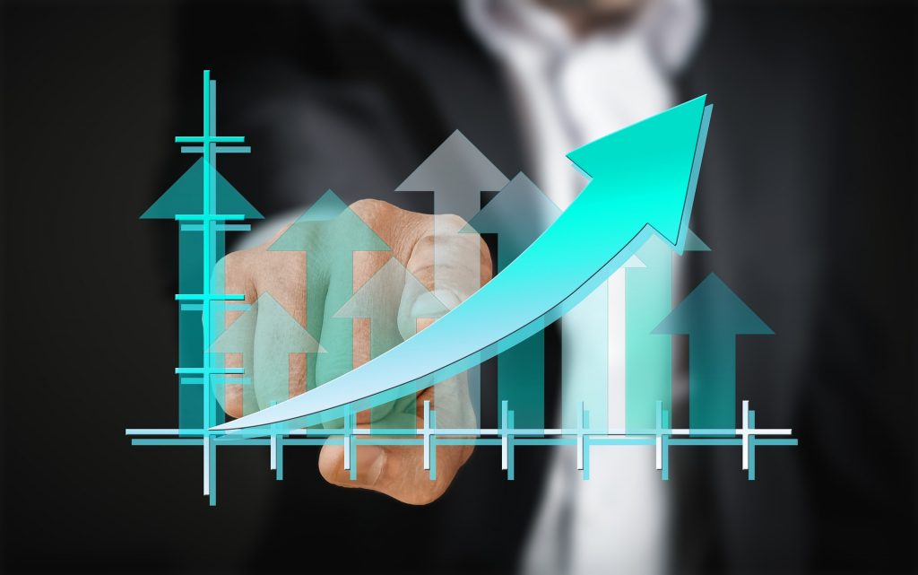 Businessman pointing to graph showing growth and improvement.