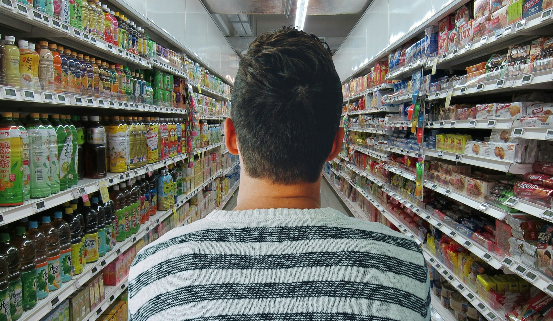 man standing in isle of a grocery store.